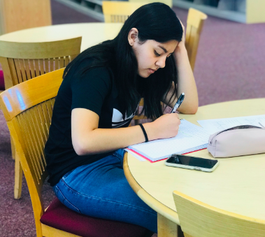 Eva Ledesma, an 11th grader at Segerstrom, diligently studies for her math class by solving problems in her notebook.