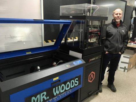 Mr. Woods is standing next to one of his various laser cutters and 3D printers that he has in his classroom. Photo Courtesy of: Jasmine Castro