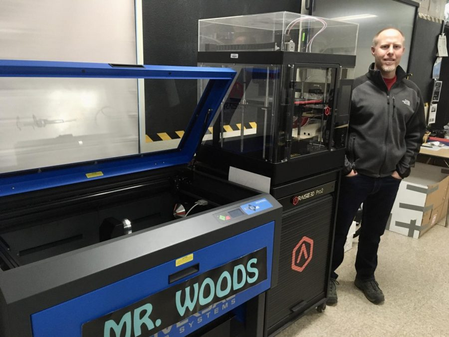 Mr.+Woods+is+standing+next+to+one+of+his+various+laser+cutters+and+3D+printers+that+he+has+in+his+classroom.+Photo+Courtesy+of%3A+Jasmine+Castro