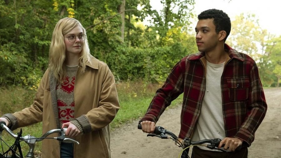 Violet (Elle Fanning) and Finch (Justice Smith) walking together in the woods.