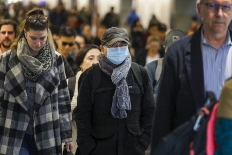 Some travelers wear masks to avoid the virus being passed on. Photo Courtesy of: Los Angeles Times