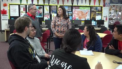 The Higher Education Center Coordinator, Mrs. Huezo, stands in front of a group of Segerstrom students.