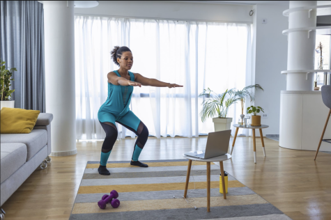 A woman is squat pulsing while watching a youtube workout video.  Photo courtesy of: Women's Health