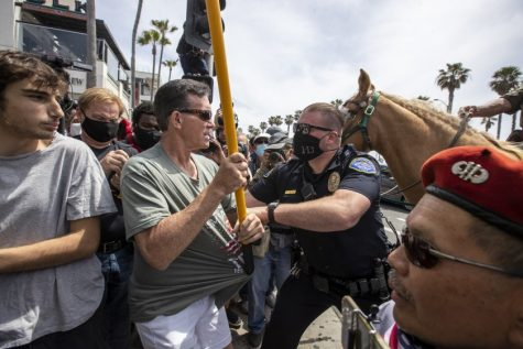 Police officer attempts to prevent violence. Photo courtesy of: Los Angeles Times.