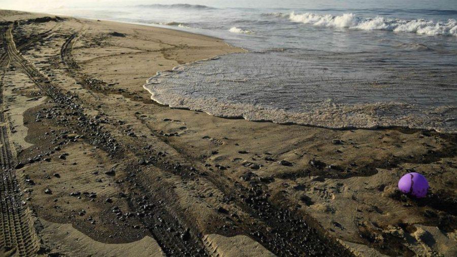 Oil washed up on Huntington Beach sand. (Image courtesy of Raul Roa, LA Times)